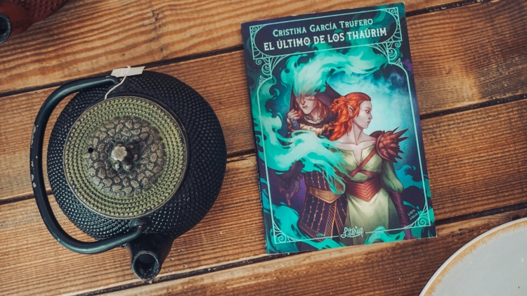 Fotografía de la novelette 'El último de los thaûrim' sobre una mesa de madera. A la izquierda hay una tetera de metal