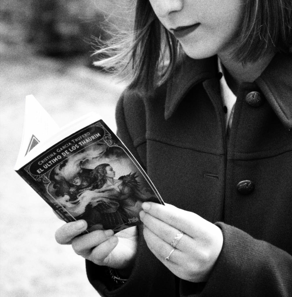 Fotografía en blanco y negro en la que se me ve solo de nariz para abajo. Estoy leyendo 'El último de los thaûrim'