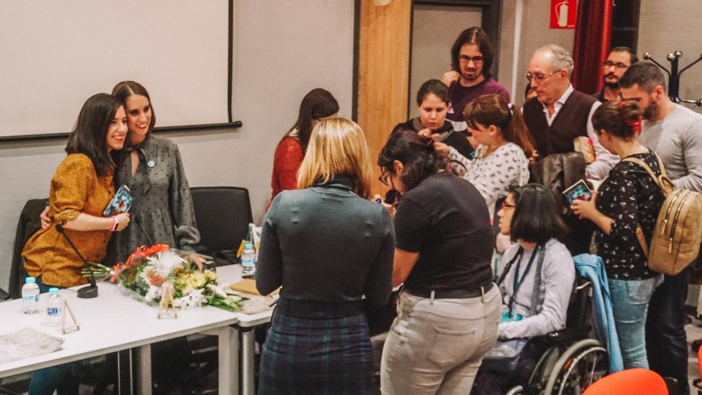 Fotografía realizada durante la presentación de 'El último de los thaûrim' en la que estoy posando con Sonia Lerones detrás de la mesa y se ve un grupo de gente esperando para que la firma